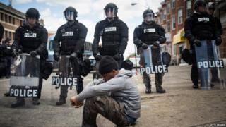 A black man sits in front of Baltimore riot police stand guard 28 April 2015