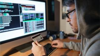 Un hombre sostiene una tarjeta de crédito frente a un monitor.