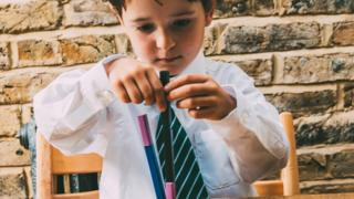 Child building blocks in school uniform