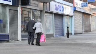 A couple walk past closed shops
