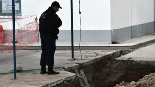 A policeman looks at the hole where the unexploded bomb was found in Thessaloniki (08 February 2017)
