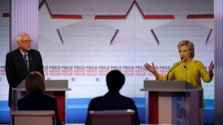 Democratic U.S. presidential candidate former Secretary of State Hillary Clinton speaks as Senator Bernie Sanders listens at the PBS NewsHour Democratic presidential candidates debate