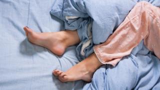 Piernas sobre una cama