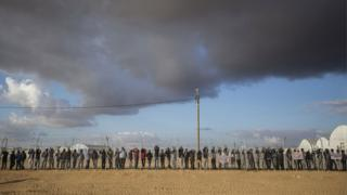 Asylum seekers stage a protest by leaning against the fence of the Holot detention centre