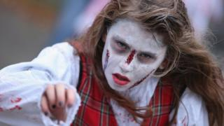 A woman with her face caked in white and with red painted scratches on her face stares lifelessly reaching forward, imitating a zombie.