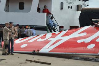Foreign investigators (L) examine the tail of the AirAsia flight QZ8501 in Kumai on 12 January 2015, after debris from the crash was retrieved from the Java sea