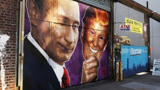 A mural depicting a winking Vladimir Putin taking off a Donald Trump mask is painted on a storefront in Brooklyn, New York City