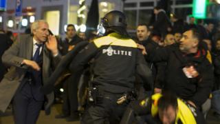Un policía holandés intenta controlar una protesta de turcos en Rotterdam.
