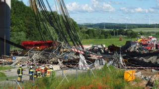 Firefighters stand near a collapsed scaffolding at a highway bridge near Werneck northern Bavaria, Germany Wednesday June 15, 2016. German news agency dpa is reporting that the scaffolding has collapsed on a highway bridge that was under construction in southern Germany.