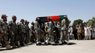 Afghan security forces carry the coffin of an Afghan soldier, who was killed last night during gun fighting between Afghan border forces and Pakistani forces in Torkham, during his funeral in Nangarhar province