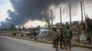 "Syrian government forces look at smoke billowing from Aleppo""s thermal power plant after they took control of the area on the eastern outskirts of Syria""s northern embattled city from Islamic State (IS) group fighters on February 21, 2016"