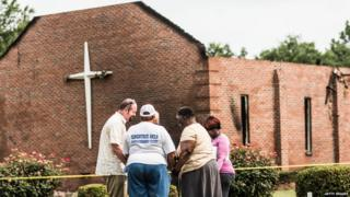 People pray near the burnt ruins of the Mt Zion AME Church in Greeleyville, South Carolina. Mt Zion was the seventh black church to burn in the southern US in less than two weeks