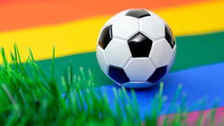 футбольный мяч на радужном флаге