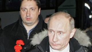 """This file photo taken on December 21, 2010 shows then Russian Prime Minister Vladimir Putin (R) and Russia""""s football supporters association head Alexander Shprygin walking to lay flowers at the grave of slain Spartak Moscow fan Yegor Sviridov in Moscow"""