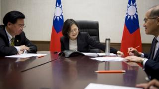 Photo released by Taiwan Presidential Office Saturday, Dec. 3, 2016, Taiwan's President Tsai Ing-wen, center, flanked by National Security Council Secretary-General Joseph Wu, left, and Foreign Minister David Lee, speaks with U.S. President-elect Donald Trump through a speaker phone in Taipei, Taiwan.