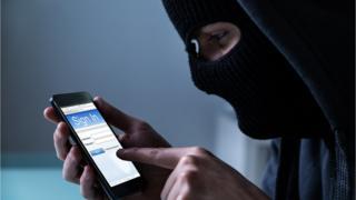 Hombre con máscara negra tiene un celular en las manos.