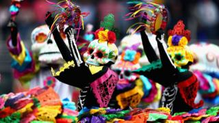 Dancers wearing pinks, yellows, blacks, reds and greens and large skulls dance with tambourines.