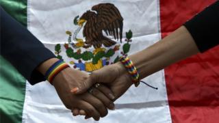 Manos entrelazadas con una bandera mexicana.