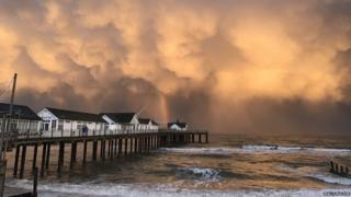 Storm clouds and a rainbow by a pier
