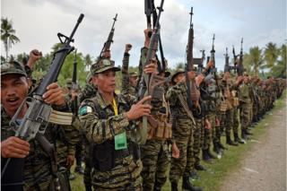 Moro Islamic Liberation Front (MILF) rebels celebrate the signing of a peace agreement during a rally at Camp Darapanan in the town of Sultan Kudarat on the southern Philippine island of Mindanao on 27 March 2014.