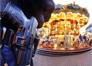 A German police officer stands next to a merry-go-round in the Christmas market in Frankfurt, Germany, 20 December