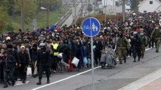 Slovenian police and army escort migrants from the train station to a registration point in the village of Sentilj, Slovenia, October 28, 2015