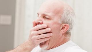 older man yawning