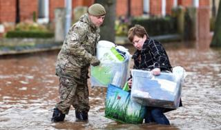 Woman being helped in flood