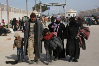 Syrian refugees walk at a Turkish border crossing