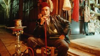 Old man smoking hookah pipe