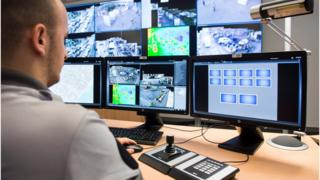 policeman watching surveillance monitors in Geneva