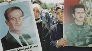 Syrian women carry portraits of Hafez and Bashar al-Assad in Damascus in June 2000