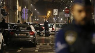 Police guard a check point and man positions during a police raid in the suburb of Schaerbeek in Brussels on 25 March