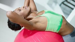 Mujer haciendo abdominales con un balón suizo