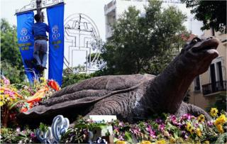 A worker installs banners marking the millennium anniversary of Hanoi next to a model of the capital's Hoan Kiem lake legendary turtle on display in the centre of Hanoi on 30 September 2010
