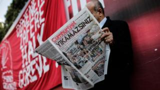 "A man reads a copy of the latest edition of the Turkish daily newspaper ""Cumhuriyet"" during a demonstration outside the newspaper's headquarters in Istanbul on November 2,2016."
