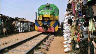 A Kenyan, selling second-hand shoes, on 18 September looks at a moving train in the Sinai slum of Nairobi.