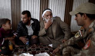 A group of civilians sit, eat and smoke cigarettes with Iraqi soldiers in eastern Mosul (1 November 2016)