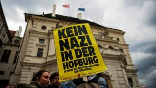 "A protestor holds a sign reading ""No Nazi in Hofburg palace"""