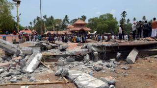 People gather near damaged buildings at the spot where a massive fire broke out during a fireworks display at the Puttingal temple complex in Paravur, southern India, 10 April 2016