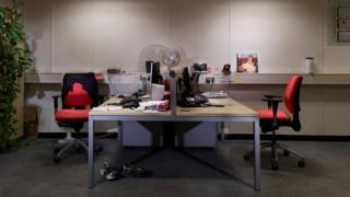 a desk with two office chairs, one side is very cluttered and the other is empty