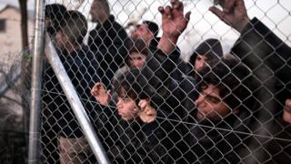 Refugees look through fence towards Macedonian side at the Greek border near village of Idomeni. 1 March 2016