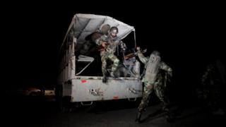 Pakistani troops jump from a vehicle outside the Police training centre, at night, during the Quetta attack in Pakistan on 25 October 2016.