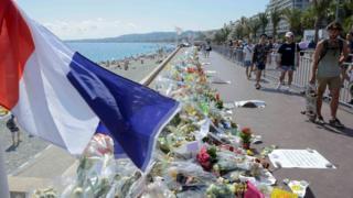 海外沿いにある遊歩道の事件現場には、犠牲者を悼む花束が手向けられている(21日、南仏ニース)
