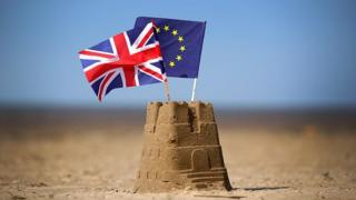The flag of the European Union and the Union flag sit on top of a sand castle on a beach