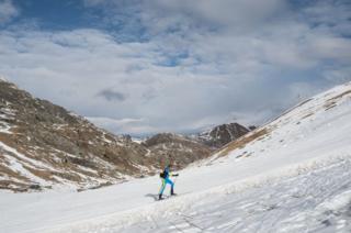 A cross country skier climbs a mountain.