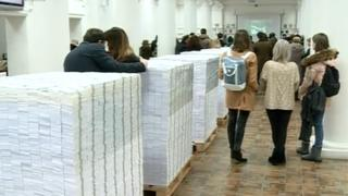 People standing among the piles of fake cash in the library