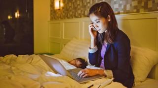 Una persona usando su laptop en mitad de la noche en la cama