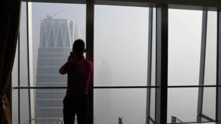 Hombre mirando la nube de contaminación en Pekín.