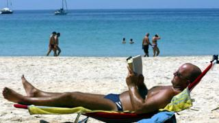 A tourist rests on a lounger on a beach in Phuket
